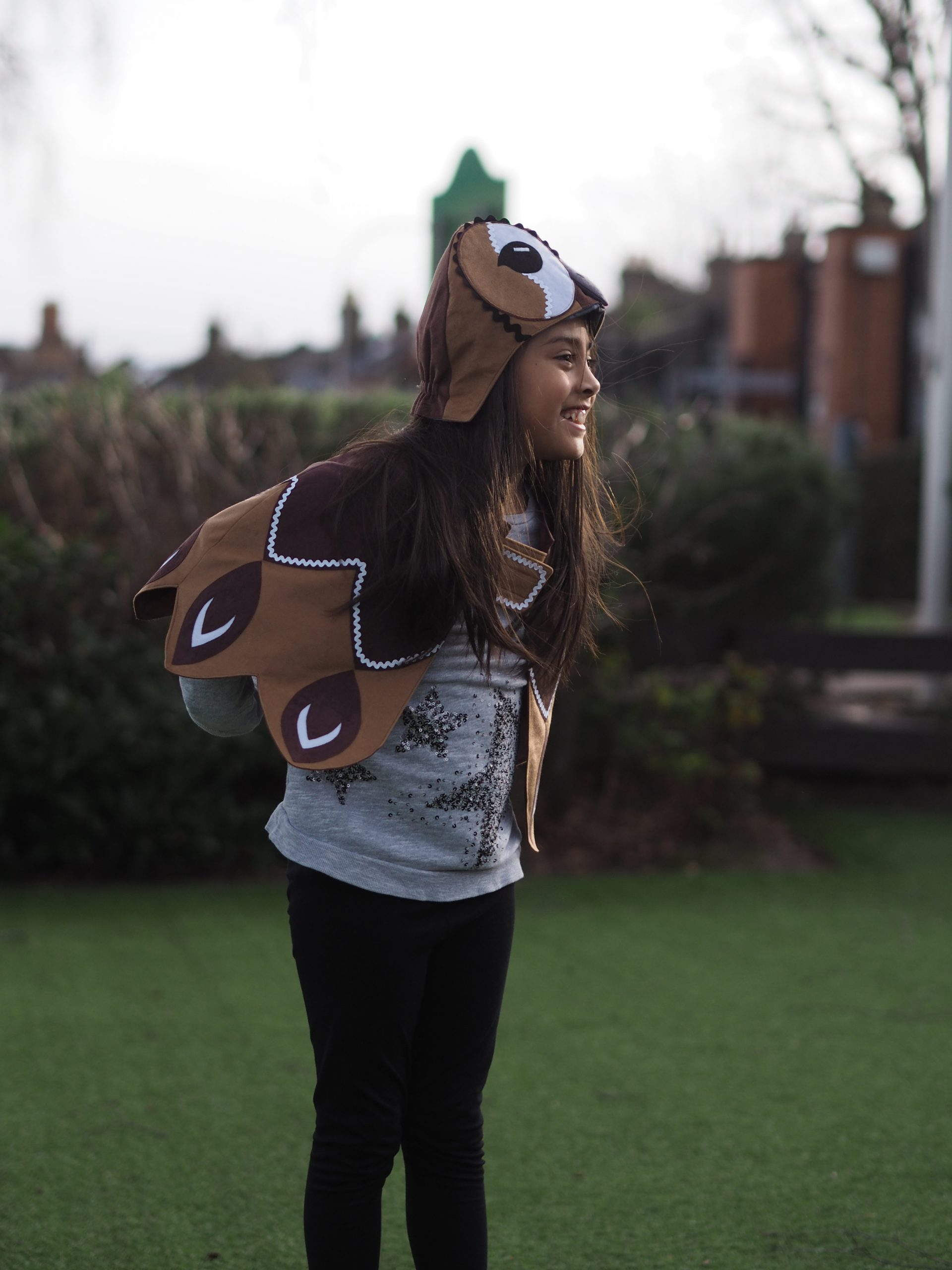 A girl is wearing a tawny owl hood and cape.