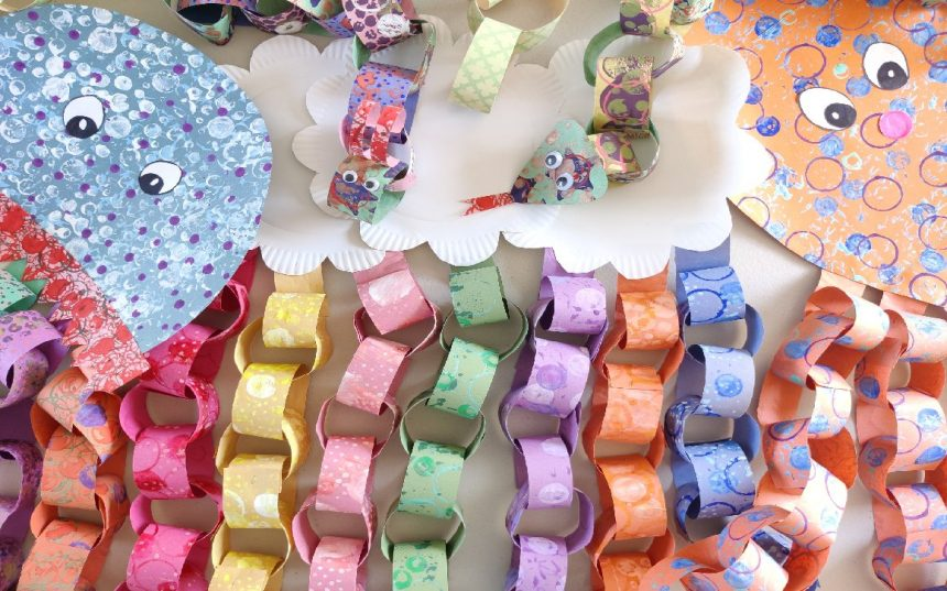 Selection of colourful paper chain crafts including a jellyfish, rainbow and clouds, caterpillar, snake and octopus