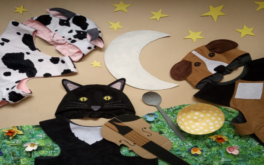 Flat lay image of Hey Diddle Diddle characters. Cow costume, cat costume and dog costume surrounded by cardboard moon and stars, cardboard violin and cardboard bowl and spoon.
