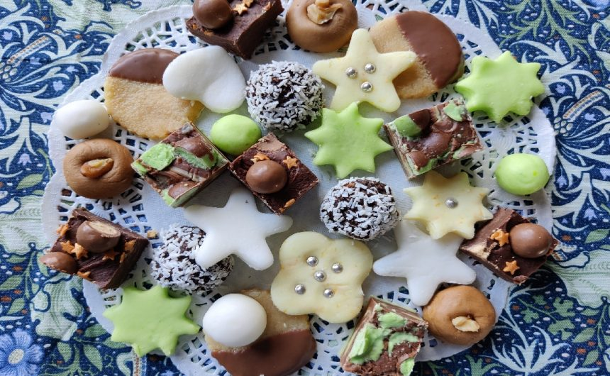 Selection of homemade sweets on a white doyley placed on a printed William Morris design table cloth. The sweets include peppermints, orange creams, coffee creams marzipan, mint chocolate fudge, ginger chocolate truffles and Maltesers fudge.